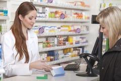 Druggist συμβουλεύεται τον πελάτη Στοκ Φωτογραφία