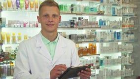 Druggist χρησιμοποιώντας την ταμπλέτα και χαμογελώντας στη κάμερα κοντά επάνω στοκ φωτογραφία