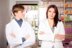 Druggist and client in front of pharmacy table. Drugs and pills in the background. Medical background Stock Photo