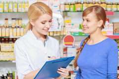 Druggist and a customer with  clipboard. Medication list. Pretty young pharmacist puts down information from a client holding a blue clipboard Stock Photo