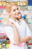 Druggist holds a blister of pills. Best treatment. Portrait of a young beautiful smiling pharmacist holding a blister of pills Stock Photos