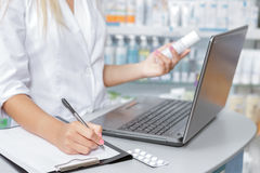 Druggist making notes from the laptop. Close up of a druggist making notes from the laptop Royalty Free Stock Image