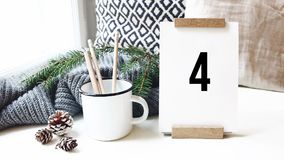 10 drugi odliczanie Kalendarz, sosna rożki i kubek z ołówkami stoi na bielu stole w wygodnym domu, biuro _ zbiory