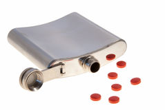 Drugs. Empty, metal hip flask lying down with a collection of red pills, isolated on white royalty free stock images