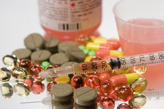 Drugs. Colorful drugs, syringe and syrup on a mirror with reflection Royalty Free Stock Image