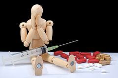 Drugs addiction. Wooden mannequin, feeling bad (about its addiction Royalty Free Stock Image
