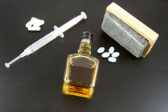 Drugs and Alcohol. Pills with a syringe, booze bottle and an eraser on a blackboard Stock Photo