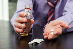 Drugs and alcohol. Man in suit with drugs and alcohol in hands Stock Photos