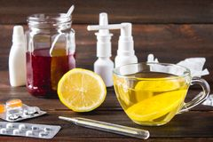 Drugs for colds - pills, spray. Folk remedies - lemon, tea, raspberry jam. Thermometer, handkerchiefs. Treatment of illness, influ Royalty Free Stock Photography