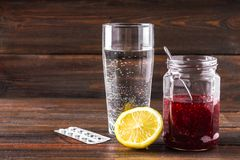 Drugs for colds - pills, spray. Folk remedies - lemon, tea, raspberry jam. Thermometer, handkerchiefs. Treatment of illness, influ. Drugs for colds - pills Royalty Free Stock Photos