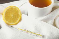 Drugs for colds - pills, spray. Folk remedies - lemon, tea, raspberry jam. Thermometer, handkerchiefs. Treatment of illness, influ. Enza. Warm scarf around the Royalty Free Stock Photography
