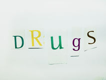 Drugs - Cutout Words Collage Of Mixed Magazine Letters with White Background. Caption composed with letters torn from magazines with White Background Royalty Free Stock Photo