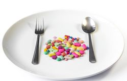 Drugs on a dish with spoon and fork Stock Photos