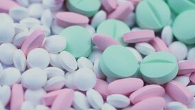 Round green and pink white narcotic drugs lie together on a table and rotate