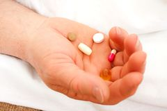 Drugs in hand. An elderly man holding different pills and drugs in his hand Royalty Free Stock Photos