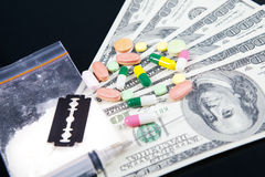 Drugs and money. Close up of drugs, money and razor blade Royalty Free Stock Photo