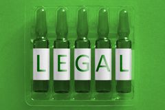Drugs nacrotics medicine concept image. Five ampules with overlay letters of inscription LEGAL. Narcotics addict or medicine drugs royalty free stock photos