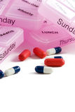 Drugs and Organizer. Medications and organizer.  Red tablet and blue and white capsule drugs lying in front of pink pillboxes .  The organizers are labeled with Stock Photography