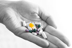 Drugs Over Black And White!. Hand in black and white holding colored drugs Stock Photo