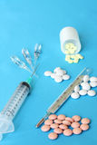 Drugs, pharmacy pills, syringe, thermometer. On the blue background Stock Photo