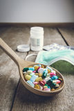 Drugs pill on wooden spoon for your treatment your health Royalty Free Stock Photography