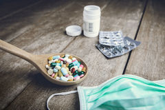 Drugs pill on wooden spoon for your treatment your health Stock Photos