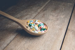 Drugs pill on wooden spoon for your treatment your health Royalty Free Stock Photo