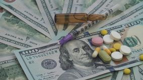 Drugs and pills for addiction lie on the thousands of paper dollars. The frame rotates counterclockwise.