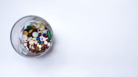 Drugs and pills. Drugs in a glass in front of white background Royalty Free Stock Photos