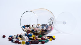 Drugs and pills. Glass of drugs, spilled out in front of white background Royalty Free Stock Photography