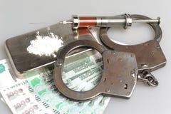 Drugs, spuit met bloed, handcuffs en geld op grijs Stock Fotografie