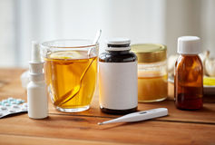 Drugs, thermometer, honey and cup of tea on wood Royalty Free Stock Photo