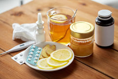 Drugs, thermometer, honey and cup of tea on wood Royalty Free Stock Images
