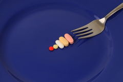 Drugs and vitamins by fork Royalty Free Stock Image
