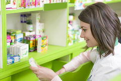 Drugstore. Young female pharmacist in a drugstore reading a receipe royalty free stock photos