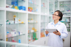 In drugstore. Asian pharmacist with digital tablet working in drugstore royalty free stock photo