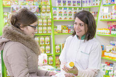 Drugstore Customer. Young female pharmacist in a drugstore having conversation with a customer stock photography