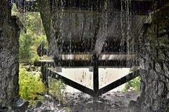 Druipende stroom van water aan het eind van tunnel waar houten is Stock Foto