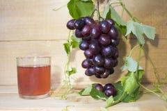 Druiven bruine achtergrond Druiven met groene bladeren Een bos van druiven mening van hierboven in groene bladeren Glas met sap Royalty-vrije Stock Afbeeldingen