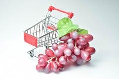Druiven en klein boodschappenwagentje op een witte achtergrond Stock Afbeeldingen