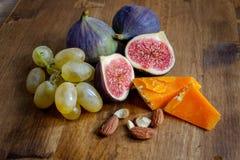 Druiven, fig., amandelen en kaas in een bos stock afbeeldingen