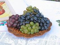 Druiven op een houten plaat met patroon Stock Foto's