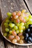 Druiven op een plaat op een oude houten lijst stock foto's