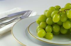 Druiven op een witte plaat stock afbeeldingen