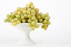 Druiven op porseleinschotel stock afbeeldingen