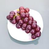 Druiven op schotel stock foto's