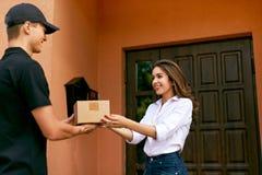 Druk de leveringsdienst uit Koerier die pakket leveren aan vrouw stock fotografie