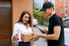 Druk de leveringsdienst uit Koerier die pakket leveren aan vrouw royalty-vrije stock foto