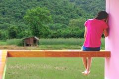 Druk en hopeloze meisjeszitting openlucht in stock foto