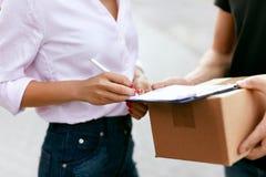 Druk levering uit Koerier die pakket leveren aan vrouw royalty-vrije stock foto's